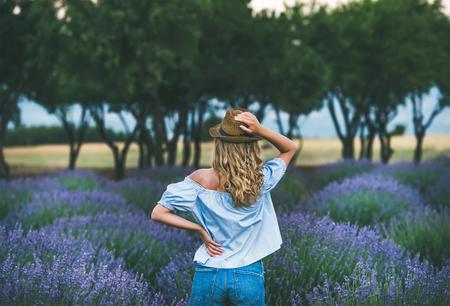 麦わら帽子、デニムのショート パンツとリアビュー、トルコのウスパルタ地域のラベンダーの花に囲まれたラベンダー畑に立っているブルーの肩か 写真素材