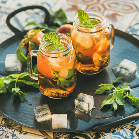 Summer refreshing cold peach ice tea with fresh mint in glass jars on metal tray over oriental ceramic tile background, selective focus, square crop