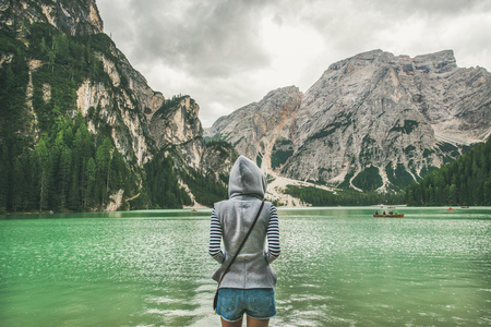 Young woman traveller in hoodie standing and looking at Lago di Braies or Pragser Wildsee in Fanes-Sennes-Braies Nature Park. Mountain lake with emerald waters in Dolomite Alps in North Italy