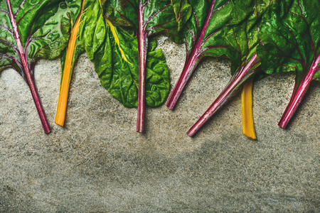 Flat-lay of fresh colorful leaves of swiss chard over concrete stone background, copy space, top view. Food frame. Clean eating, vegan, vegetarian, alcaline diet, organic, healthy cooking concept Stock Photo