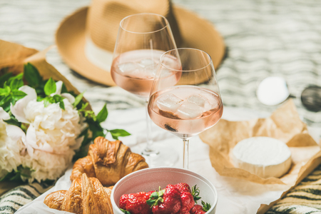 French style romantic summer picnic setting. Flat-lay of glasses of rose wine with ice, fresh strawberries, croissants, brie cheese, straw hat, sunglasses, peony flowers. Outdoor gathering concept Stock Photo