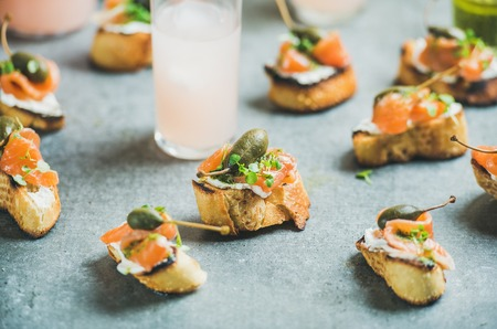 Crostini with smoked salmon, pesto sauce, watercress and capers and pink grapefruit cocktails over grey background, selective focus. Party, catering or fingerfood concept