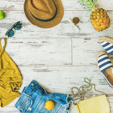Colorful fashion outfit flat-lay. Denim shorts, straw hat, yellow top, espadrillas, leather bag, sunglasses, pineapple, limes, lemon over pastel parquet background, top view, square crop copy space