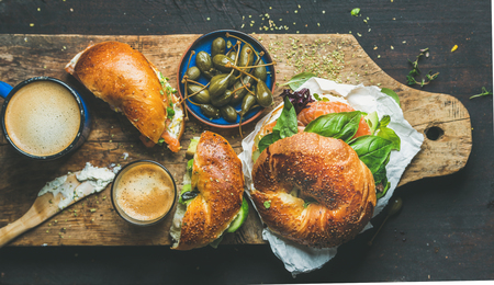 Breakfast with bagel with salmon, avocado, cream-cheese, basil, espresso coffee in blue mug, capers in bowl, rustic wooden board over dark scorched background, top view. Healthy or diet food concept