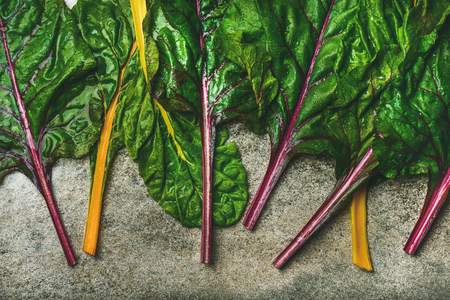 Flat-lay of fresh leaves of swiss chard over concrete stone background, top view. Clean eating, vegetarian, alcaline diet, organic, healthy cooking concept
