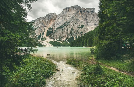 Lago di Braies or Pragser Wildsee in Fanes-Sennes-Braies Nature Park. Mountain lake with clear emerald waters surrounded by forests in Valle di Braies in Dolomite Alps in North Italy on gloomy day 版權商用圖片