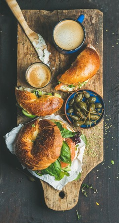 Breakfast with bagel with salmon, avocado, cream-cheese, basil, espresso coffee, capers in blue bowl, rustic wooden board over dark scorched background, top view. Healthy or diet food concept Stock Photo