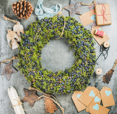 Flat-lay of Christmas decorative green wreath with fresh blueberries and natural herbs, wooden toys, presents and materials for making decoration over grey concrete background, top view, copy space