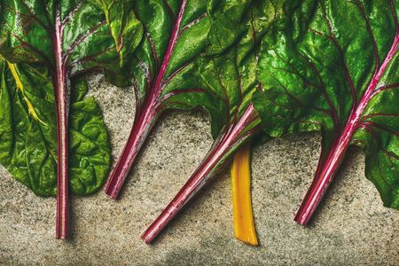Flat-lay of fresh leaves of swiss chard over concrete stone background, top view, horizontal composition. Clean eating, vegetarian, vegan, alcaline diet, organic, healthy cooking concept