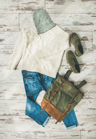 Flat-lay of Fall lady s clothes outfit. Ecru colored knitted woolen sweater with braids, blue denim jeans, haki suede oxford boots, backpack, cap over parquet background, top view. Trendy Autumn look