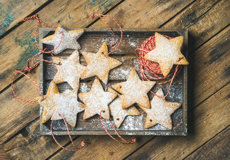 Christmas gingerbread star shaped cookies with sugar powder and decoration rope in wooden tray over rustic background, top view, horizontal composition Stock Photo