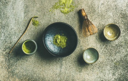 tin: Flat-lay of Japanese tools for brewing matcha tea. Matcha powder in tin can, Chashaku spoon, Chasen bamboo whisk, Chawan bowl and cups over concrete background, top view, horizontal composition