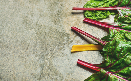 Flat-lay of fresh leaves of swiss chard over grey concrete stone background, copy space, selective focus. Food frame. Clean eating, vegan, vegetarian, alcaline diet, organic, healthy cooking concept Stock Photo