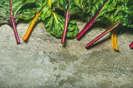 Flat-lay of fresh leaves of swiss chard over concrete stone background, copy space, horizontal composition. Food frame. Clean eating, vegetarian, alcaline diet, organic, healthy cooking concept Stock Photo - 87802028