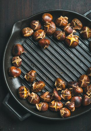Roasted chestnuts in cast iron grilling pan over dark scorched wooden background, top view, copy space, vertical composition Stock Photo