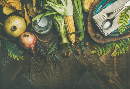 Herfsttafel instelling voor Thanksgiving-viering. Plat leggen van bord, bestek, kandelaar, herfst seizoensgroenten, fruit en gevallen bladeren voor decor over houten achtergrond, bovenaanzicht, kopie ruimte