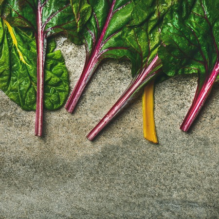 Flat-lay of fresh leaves of swiss chard over concrete stone background, copy space, top view, square crop. Food frame. Clean eating, vegan, vegetarian, alcaline diet, organic, healthy cooking concept Stock Photo