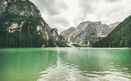 Lago di Braies or Pragser Wildsee in Fanes-Sennes-Braies Nature Park. Mountain lake with clear emerald waters in Valle di Braies in the Dolomite Alps in North Italy on gloomy day