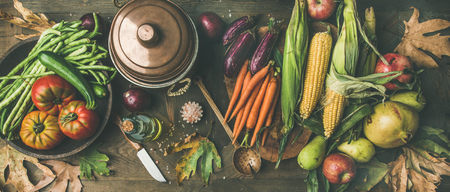 Fall healthy cooking background. Ingredients for Thanksgiving day dinner. Flat-lay of beans, corn corn, carrot, tomatoes, eggplants, fruits and fallen leaves over wooden table, top view Imagens