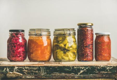 秋の季節のピクルスや、ヴィンテージキッチンの引き出し、白い壁の背景、コピースペースの上に行に配置された瓶のカラフルな野菜を発酵させま 写真素材