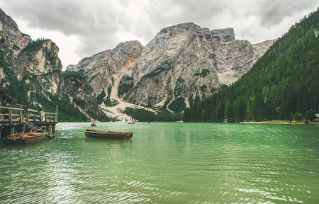Lago di Braies or Pragser Wildsee in Fanes-Sennes-Braies Nature Park. Mountain lake with clear emerald waters and wooden boats in Valle di Braies in Dolomite Alps in North Italy on gloomy day