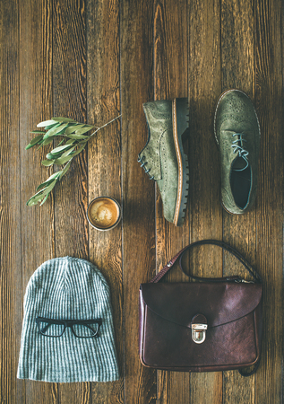 Flat-lay of womans fall accessories and coffee. Haki suede leather oxford boots, brown shoulder bag, grey cap and cup of espresso over wooden background, top view, copy space