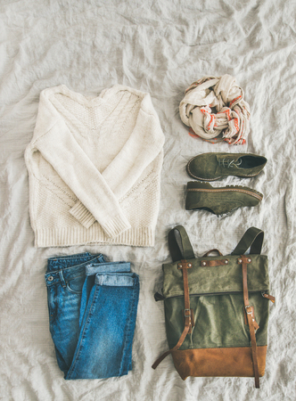Flat-lay of Fall lady' s clothes outfit. Ecru colored knitted woolen sweater, linen scarf, denim jeans, haki suede boots, backpack over grey linen bed blanket, top view, copy space. Trendy Autumn look Stok Fotoğraf - 87875743