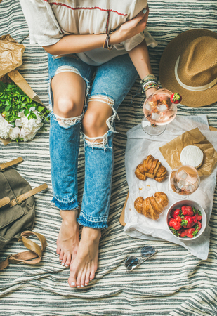 French style romantic picnic setting. Woman in denim pants sits with glass of ice rose wine, strawberries, croissants, brie cheese, hat, sunglasses, peony flowers, top view. Outdoor gathering concept Stock Photo