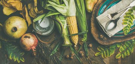 Impostazione della tavola caduta per la celebrazione del Ringraziamento. Piatto-lay di piastra, posate, portacandele, verdure stagionali autunno, frutta e foglie cadute per arredamento su sfondo in legno, vista dall'alto Archivio Fotografico - 87914139