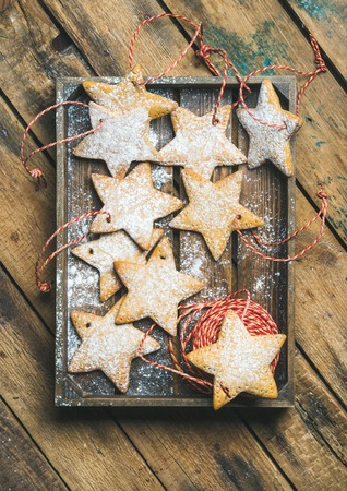 Christmas gingerbread star shaped cookies with sugar powder and decoration rope in wooden tray over rustic background, top view, vertical composition