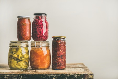 Autumn seasonal pickled or fermented colorful vegetables in glass jars placed in stack over vintage kitchen drawer, white wall background, copy space. Fall home food preserving or canning Archivio Fotografico
