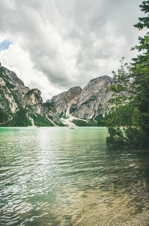 Lago di Braies or Pragser Wildsee in Fanes-Sennes-Braies Nature Park. Mountain lake with clear emerald waters in Valle di Braies in Dolomite Alps in North Italy, vertical composition