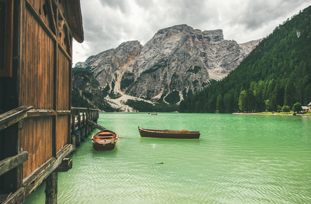 Lago di Braies or Pragser Wildsee in Fanes-Sennes-Braies Nature Park. Mountain lake with clear emerald waters and wooden boats in Valle di Braies in the Dolomite Alps in North Italy on gloomy day
