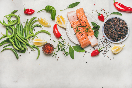 Flat-lay of raw salmon fish fillet steaks with vegetables, greens, rice and spices over grey marble background, top view, copy space. Clean eating, alkaline diet, dieting, power boosting concept