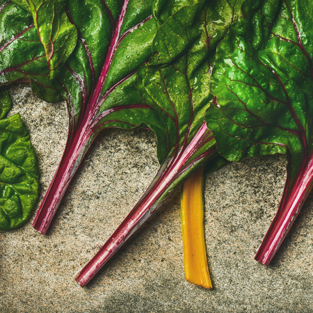 Flat-lay of fresh leaves of swiss chard over concrete stone background, top view, square crop. Clean eating, vegetarian, vegan, alcaline diet, organic, healthy cooking concept