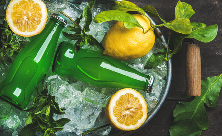 Bottles of green lemonade on chipped ice in metal tray with fresh lemons and mint over dark wooden background, top view