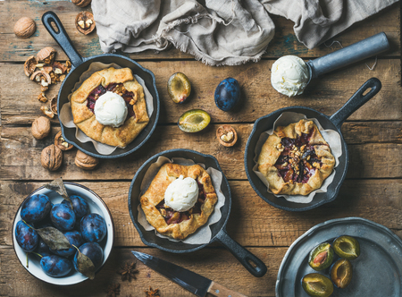 Plum and walnut crostata pie with ice-cream scoops in individual cast iron pans over rustic wooden table, top view. Slow food concept