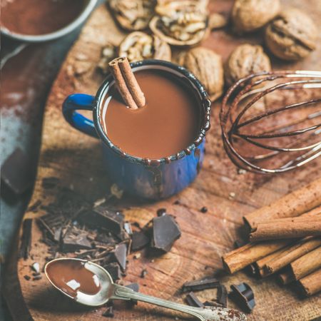 Rich winter hot chocolate with cinnamon sticks and walnuts in blue enamel mug on wooden board over grey concrete background, selective focus, square crop