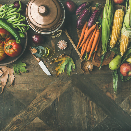 Fall cooking background. Ingredients for Thanksgiving day dinner. Flat-lay of beans, corn, carrot, tomatoes, eggplants, fruits and fallen leaves over wooden table, top view, copy space, square crop Stock Photo