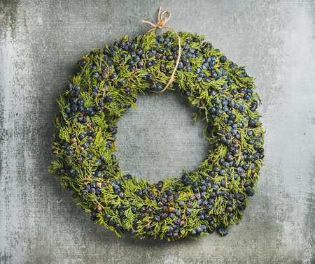 Christmas decorative green wreath with fresh blueberries and natural herbs over grey concrete wall background, horizontal composition