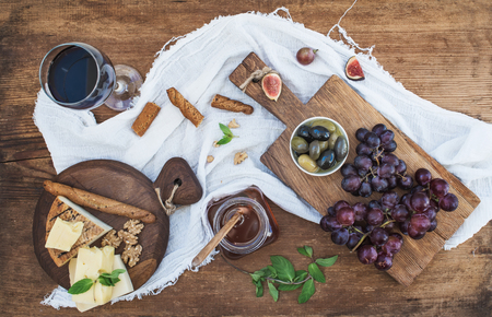 Glass of red wine, cheese board, grapes, olives, honey, walnuts and bread sticks  on rustic wooden table, top view