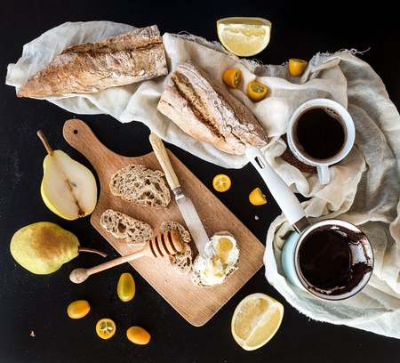 Breakfast set: a pot or cezve of coffee, a cup on a kitchen towel, kumquats, pears, grapefruit, baguette slices with butter cream and honey on rustic wooden board over  black backdrop. Top view