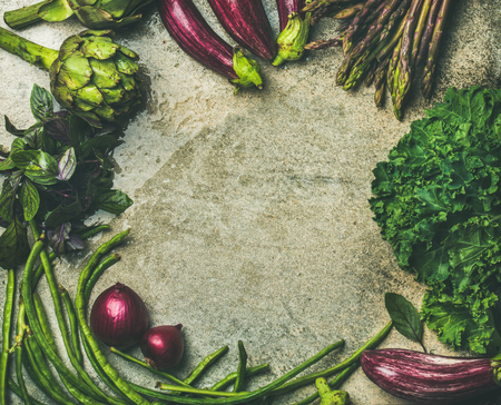 Flat-lay of green and purple vegetables over concrete background, top view, copy space, food frame. Local produce for healthy cooking. Eggplans, beans, kale, asparagus, artichoke, basil. Clean eating Stock Photo