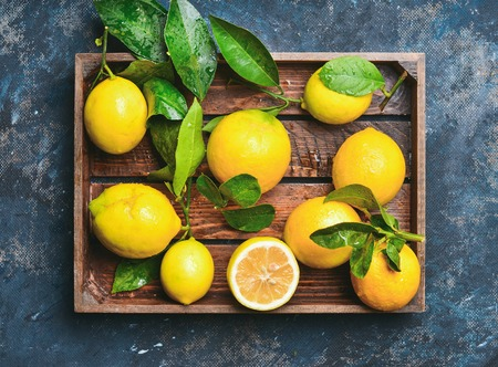 Freshly picked lemons with leaves in rustic wooden tray over dark blue shabby plywood background, top view Stock Photo