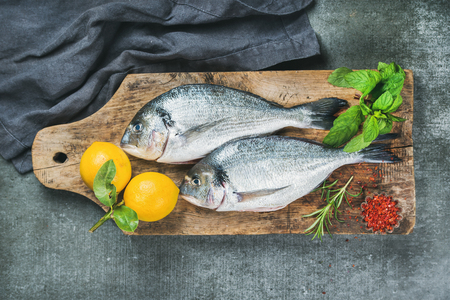 Fresh uncooked sea bream or dorado fish with lemon, herbs and spices on rustic wooden board over grey concrete background, top view. Healthy, dieting, clean eating concept Stock Photo