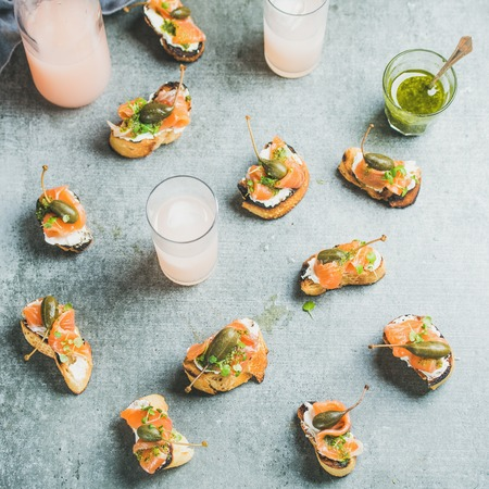 Crostini with smoked salmon, pesto sauce, watercress and capers and pink grapefruit cocktails over grey background, top view, square crop. Party, catering or fingerfood concept