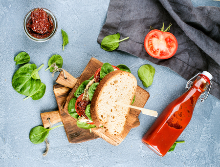 Chicken, sun-dried tomato and spinach sandwich with spicy sauce on small rustic wooden board over grey concrete textured background, top view