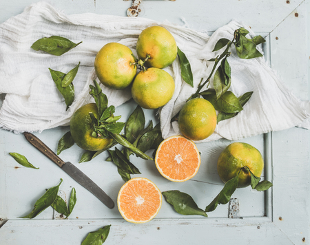 Fresh Turkish tangerines with leaves over blue rustic wooden backdrop, top view