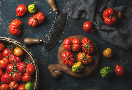 Fresh colorful ripe Fall heirloom tomatoes in basket and on wooden board, herb chopper knife for cooking over grunge dark plywood background, top view. Harvest vegetable cooking conception.