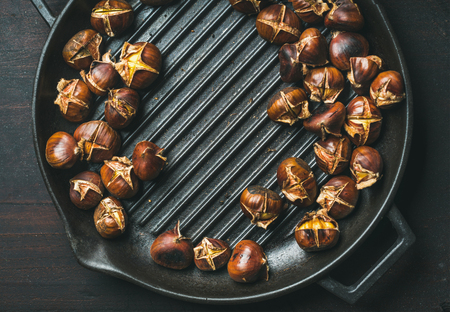Roasted chestnuts in cast iron grilling pan over dark scorched wooden background, top view, copy space Stock Photo